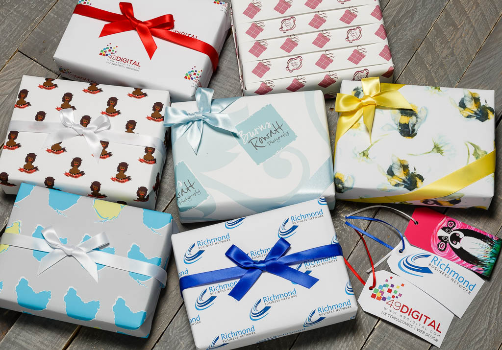 A selection of boxes wrapped in branded giftwrap with ribbons and a selection of luggage tags