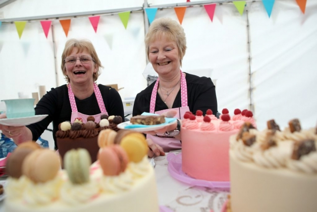 The 2 ladies in pink aprons from Kteas Tearoom surrounded by delicious cakes