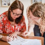 Angela, founder of Creative Calligraphy & a workshop attendee looking at a calligraphy worksheet