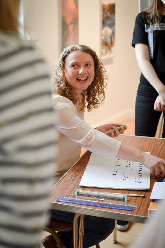 A smiling Angela, founder of Creative Calligraphy sat with a notebook and calligraphy pens