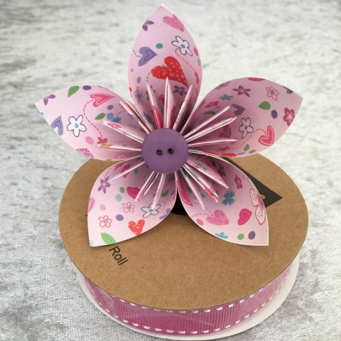 Paper flower using pink giftwrap with a purple centre button sat on top of a roll of raspberry coloured Jane Means grosgrain ribbon