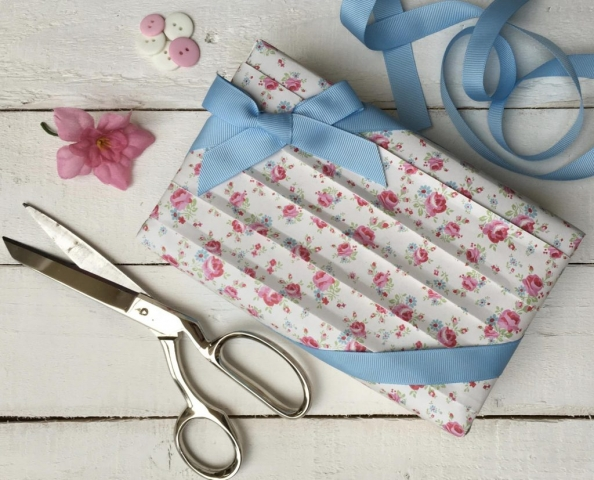 Japanese pleated parcel using tea rose paper, with a blue corner ribbon bow