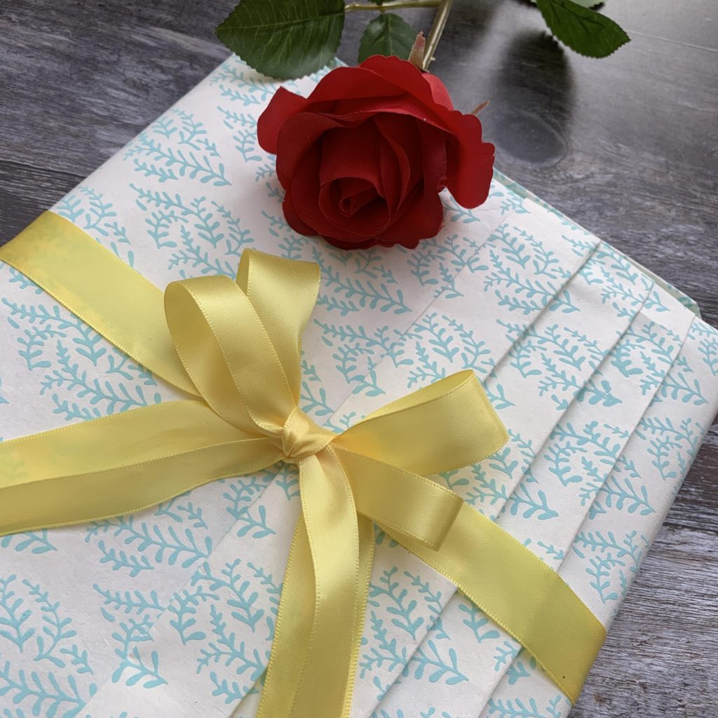 Pleated giftwrapping paper a double bow and a red rose