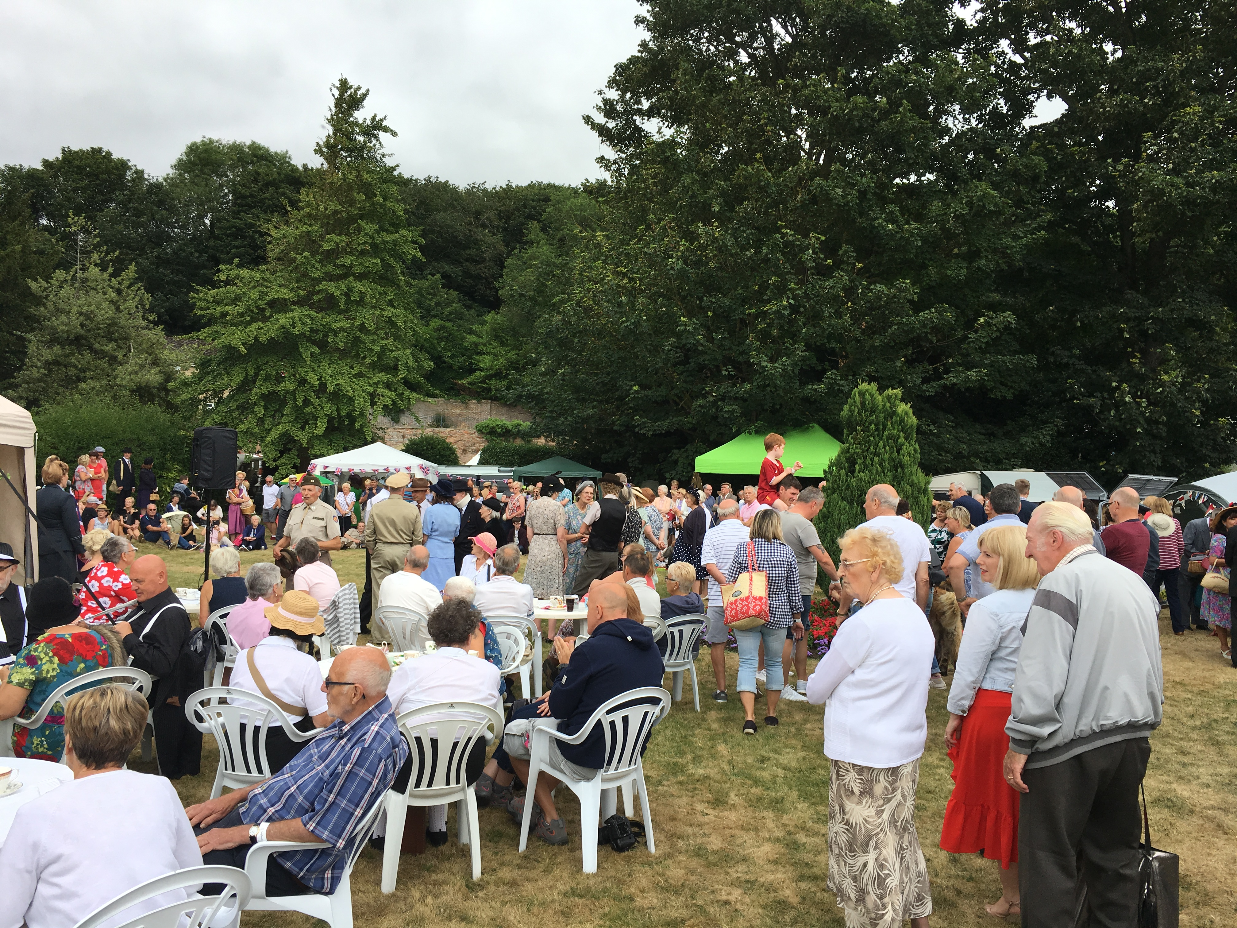 People sat at the tea-room tables and milling around on the grass outside Thornborough Hall at The Home Front Vintage Fair, 2018