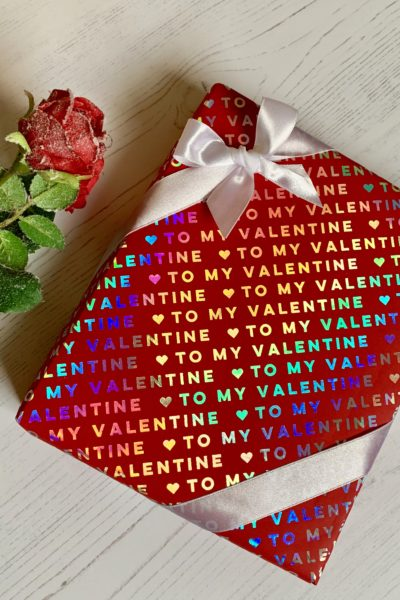 Red giftwrap with 'to my valentine' printed on it in silver foil. A white corner bow and a rose on the side
