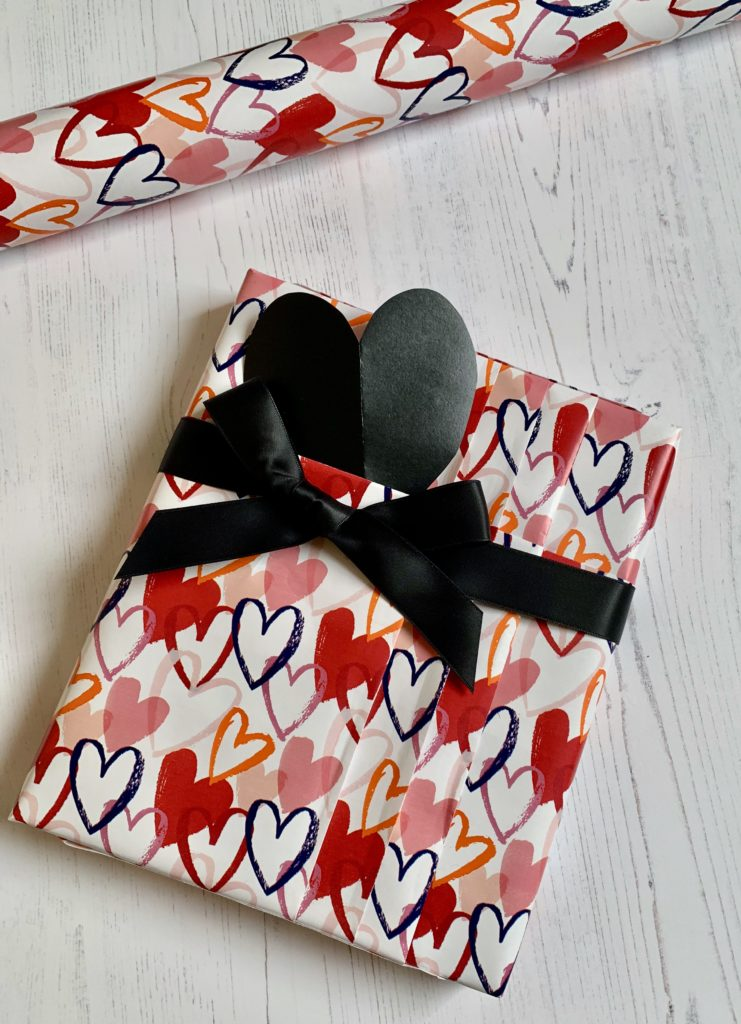 Valentine giftwrap with a pleated design, black satin ribbon and a heart shaped tag