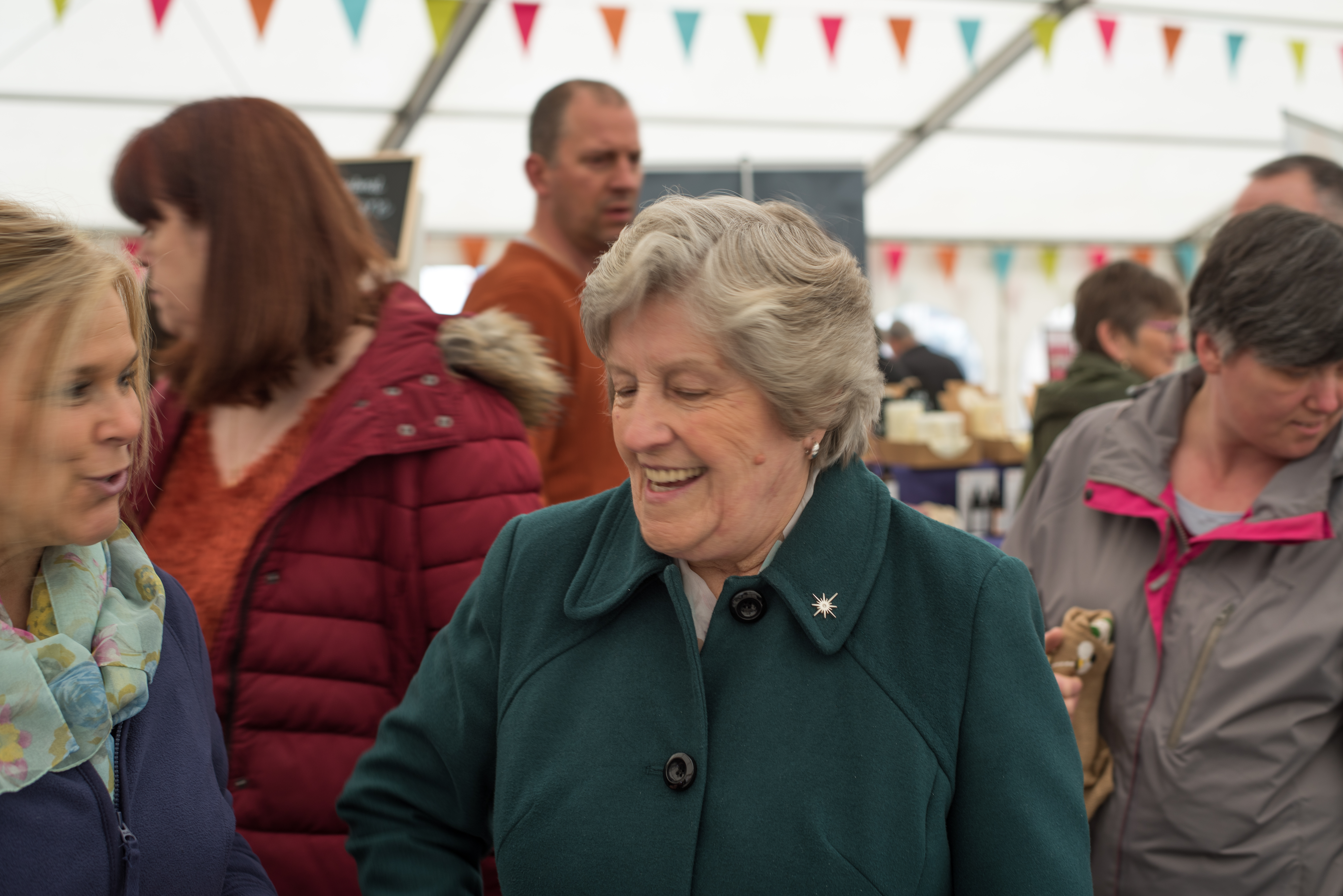 A lady in a green coat smiling as she shops inside the marquee at Stockton Chic Vintique  6th April