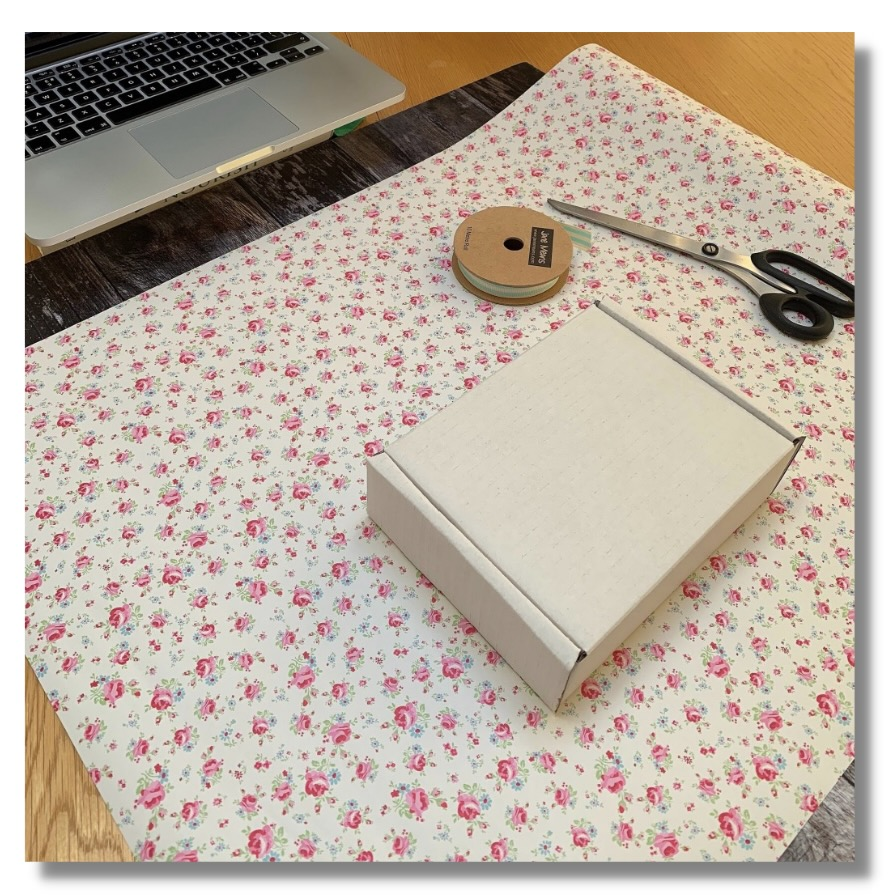 Wrapping paper, ribbon & scissors laid out ready for an online wrapping class