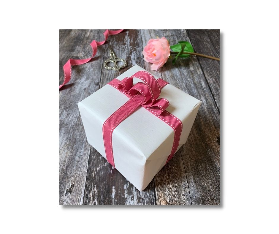 A white box with a pink bow: one of the things you would learn at a gift wrapping class